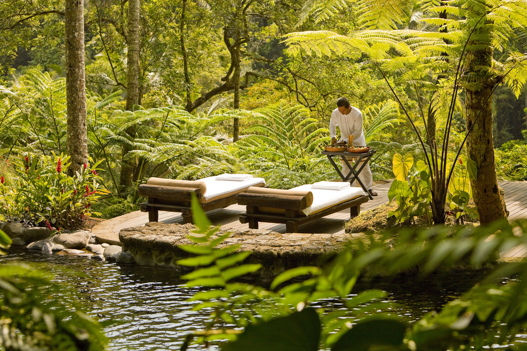 Two private lounge beds in the Bali jungle by a river with personal assistant preparing food nearby.