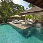 The pool of the 2 bedroom retreat villas Saundarya and Shantivana with view of outdoor terrace and lounge beds