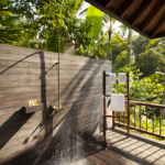 The outdoor shower of the 2 bedroom retreat villas with a towel rail and a view of the Bali jungle in the background