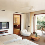 The twin bedroom of the 2 bedroom Saundarya retreat villa with TV inside and open doors leading to a patio with table and chairs