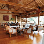 Lounge area of Como Shambhala's Bayugita residence with tables and chairs and wooden features