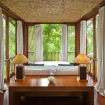 Double bed in one of the bedrooms of the Wanakasa terrace suite with panoramic views of the Bali the jungle out the floor to ceiling windows