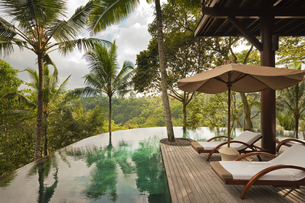 Infinity pool of the Wanakasa private residence with an adjacent terrace with lounge beds and a parasol with a backdrop of the Bali jungle.