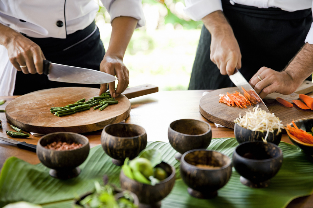 Two chefs preparing food on wooden chopping boards on a table with small wooden ramekins containing ingredients in the foreground.