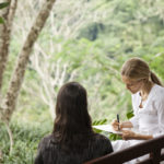 Como Shambhala's resident dietician Eve Persak holds a consultation with a guest on a bench among the Bali jungle