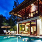 Evening view of the pool at 2 bedroom villa Gesing Kanila with living area and upstairs terrace of the villa behind and lounge beds and parasol next to the pool