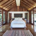 Master bedroom of Como Shambhala's Gesing Kanila 2 bedroom villa featuring bed, carpet, and floor to ceiling windows