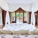 Master bedroom at the Pita Linggar 3 bedroom home featuring canopy bed and french doors leading off to a terrace with panoramic jungle views