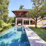 Daytime view of the infinity pool surrounded by the Bali jungle at the Pita Linggar 3 bedroom home with sun loungers and a parasol adjacent on the grass lawn