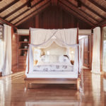 Master bedroom of the Sukma Taru 2 bedroom home with canopy style bed, wooden features and floor to ceiling windows