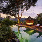 The swimming pool in the middle of the Bali jungle at the Sukma Taru 2 bedroom home at dusk surrounded by lamps highlighting the patio area with swing seating and lounge beds