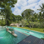 Como Shambhala's vitality pool with a man taking laps in the pool below and the Bali jungle in the background