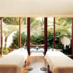 One of Como Shambhala's treatment rooms with two separate treatment beds and a relaxing tropical garden terrace in the background