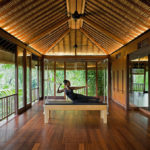 Female practising pilates in Como Shambhala's pilates studio with wooden features and a view of the Bali jungle out of the windows