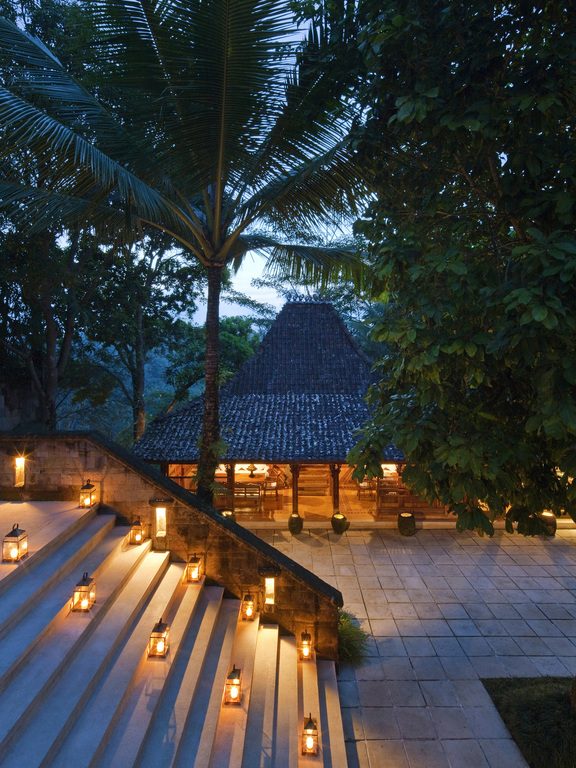 Evening view of the steps up to Kudus House restaurant at the Como Shambhala estate with lanterns on the steps and the surrounding patio.